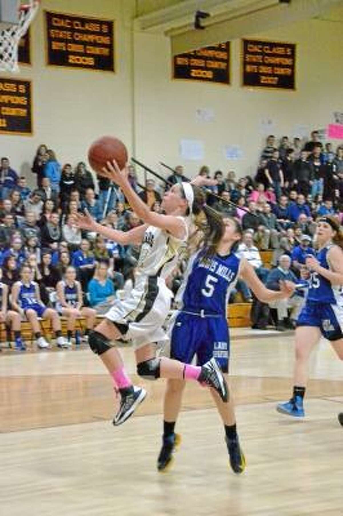 Thomaston guard Maggie Eberhardt goes up for a layup as Lewis Mills' Natalie Ruel defends.