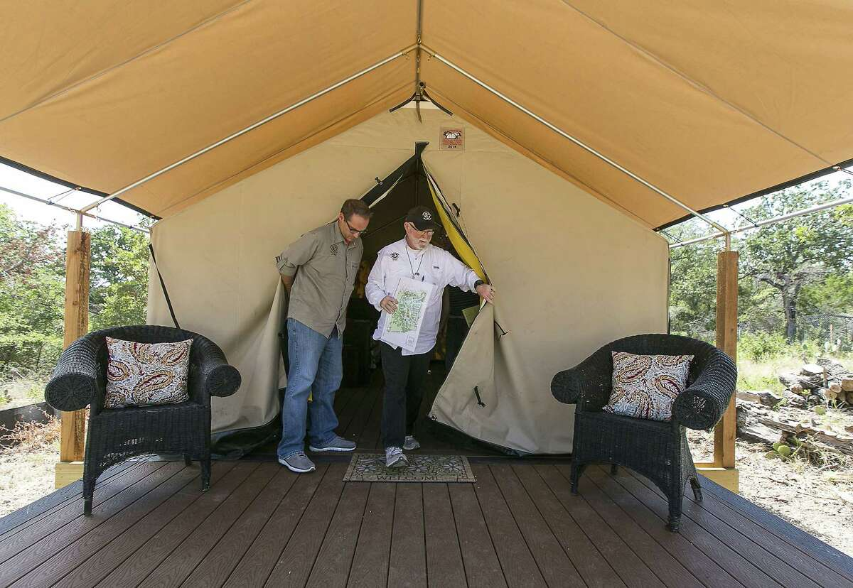 Mobile Loaves & Fishes founder and president Alan Graham, right, and Nate Schlueter, director of the Mobile Loaves & Fishes ROADS program (Relationships & Opportunities Allowing for Dignity & Security), exit a tent-like cottage that will be offered at new Community First Village just east of Austin, Texas, on Tuesday, Sept. 8, 2014. The $12 million Community First Village will not just be a place for its 225 or so otherwise-homeless tenants to live, Graham said. It will be a fully functioning community, complete with a movie screen and commissary for residents to earn a living, from the time they enter until they die, should they choose to live there until the end. (AP Photo/Austin American-Statesman, Rodolfo Gonzalez) AUSTIN CHRONICLE OUT, COMMUNITY IMPACT OUT, INTERNET MUST CREDIT PHOTOGRAPHER AND STATESMAN.COM