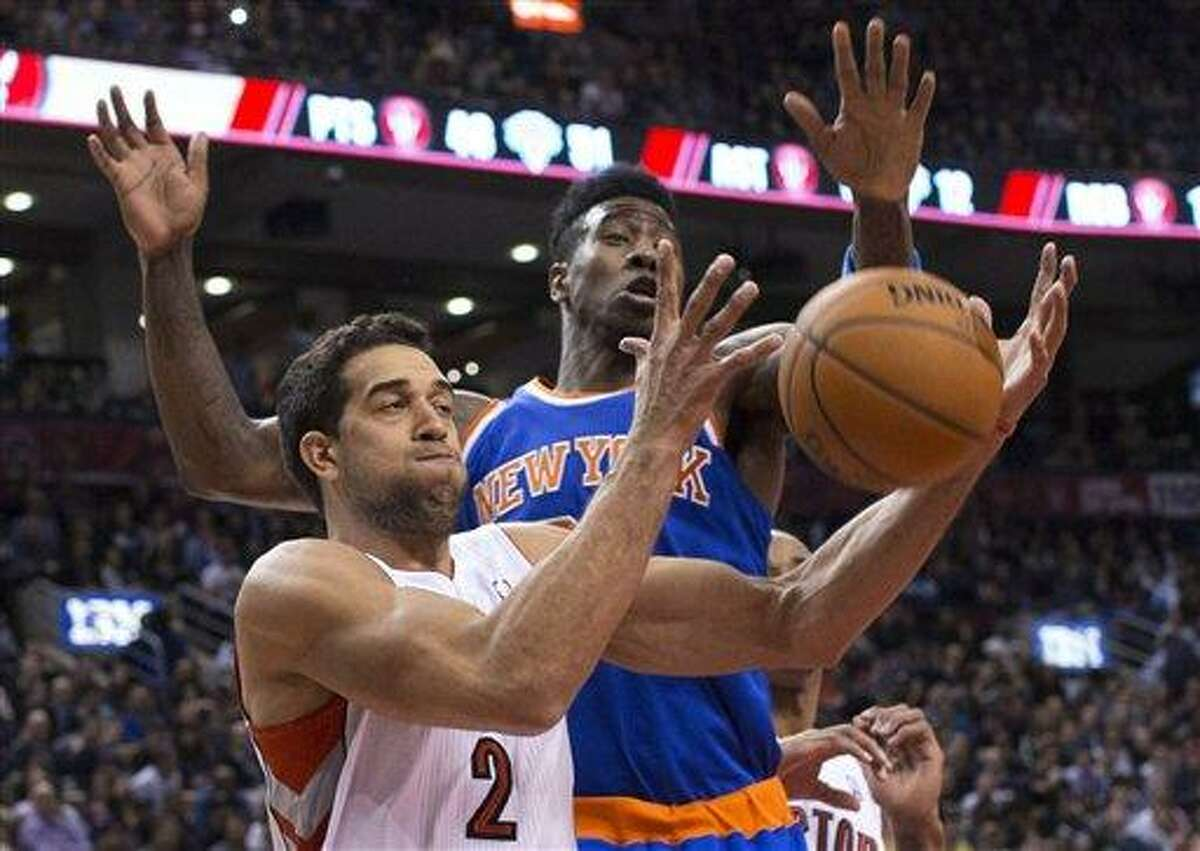 Toronto Raptors' Landry Fields, left, and New York Knicks' Iman Shumpert try to get control of the ball during the first half of an NBA basketball game in Toronto on Friday, Feb. 22, 2013. (AP Photo/The Canadian Press, Chris Young)