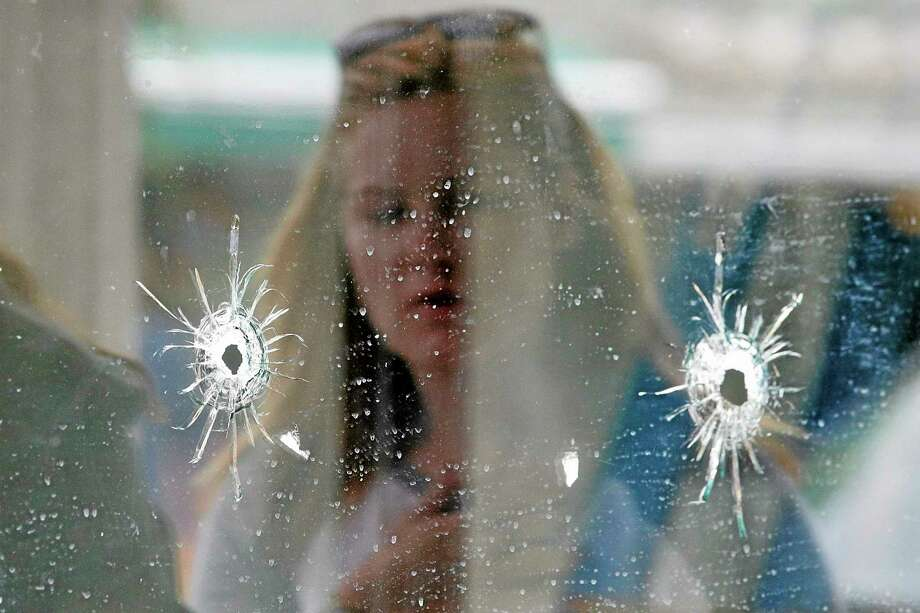 A woman looks at the bullet holes on the window of IV Deli Mark where Friday night's mass shooting took place by a drive-by shooter on Saturday, May 24, 2014, in Isla Vista, Calif. Photo: (Jae C. Hong — The Associated Press) / AP