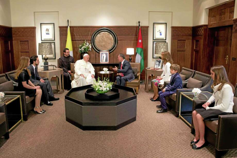 Pope Francis meets with King Abdullah II of Jordan, fourth from right, his wife Queen Rania, third from right, and their four children in Amman's Al Husseini Royal Palace, Jordan, Saturday, May 24, 2014. The pontiff is in Jordan on the first of a three day trip to the Middle East that will also take him to the West Bank and Israel. (AP Photo/Andrew Medichini, Pool) Photo: AP / AP
