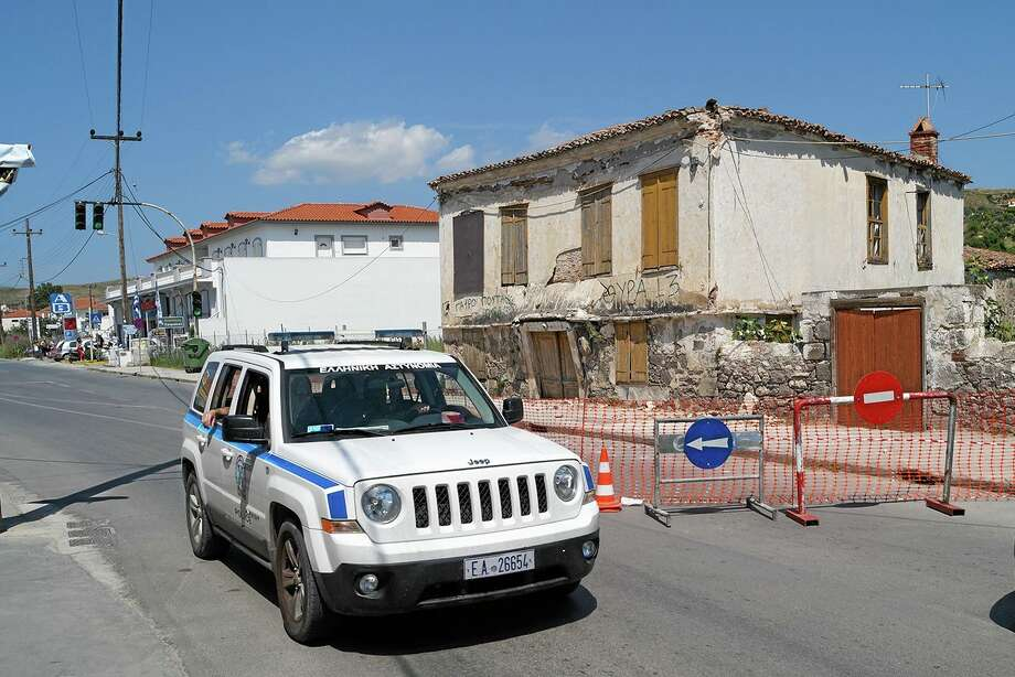 Police patrols as an old building is damaged after a magnitude 6.3 earthquake on the northeastern Aegean Sea island of Lemnos, Greece, Saturday, May 24, 2014. An earthquake beneath the sea shook northern Greece and western Turkey Saturday, with more than 100 people reportedly injured in Turkey. (AP Photo/Ayis Theos) Photo: AP / AP