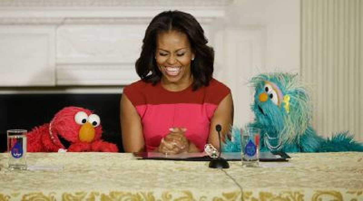First lady Michelle Obama, center, with PBS Sesame Street's characters Elmo, left, and Rosita, right, as they help promote fresh fruit and vegetable consumption to kids in an event in the State Dining Room of the White House in Washington, Wednesday, Oct. 30, 2013.