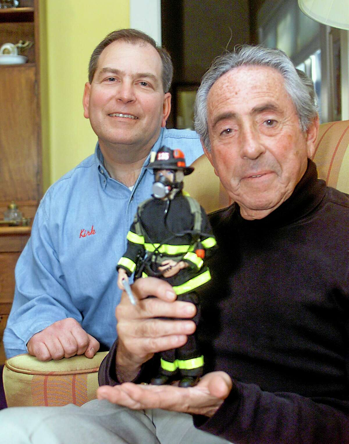 FILE - In this Dec. 7, 2001 file photo, Kirk Bozigian, left, and Don Levine, co-founders of Real Heroes Inc., show one of their collectible designs, a New York City firefighter, in Levine's home in Providence, R.I. Levine, the Hasbro executive credited as the father of G.I. Joe for developing the world's first action figure, died of cancer early Thursday, May 22, 2014, at Home & Hospice Care of Rhode Island, said his wife, Nan. He was 86. (AP Photo/Stew Milne, File)