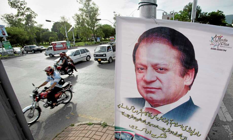 Motorists ride past a banner of Pakistani Prime Minister Nawaz Sharif hanging on an electricity pole in Islamabad, Pakistan. Sharif will attend the inauguration of India's Prime Minister-designate Narendra Modi, a first for the nuclear-armed rivals, officials said Saturday. Pakistan and India have a history of uneasy relations and they have fought three wars over the disputed Himalayan region of Kashmir since their independence from Britain in 1947. Saturday's decision by Sharif could signal a further easing of tensions. (AP Photo/Anjum Naveed) Photo: AP / AP