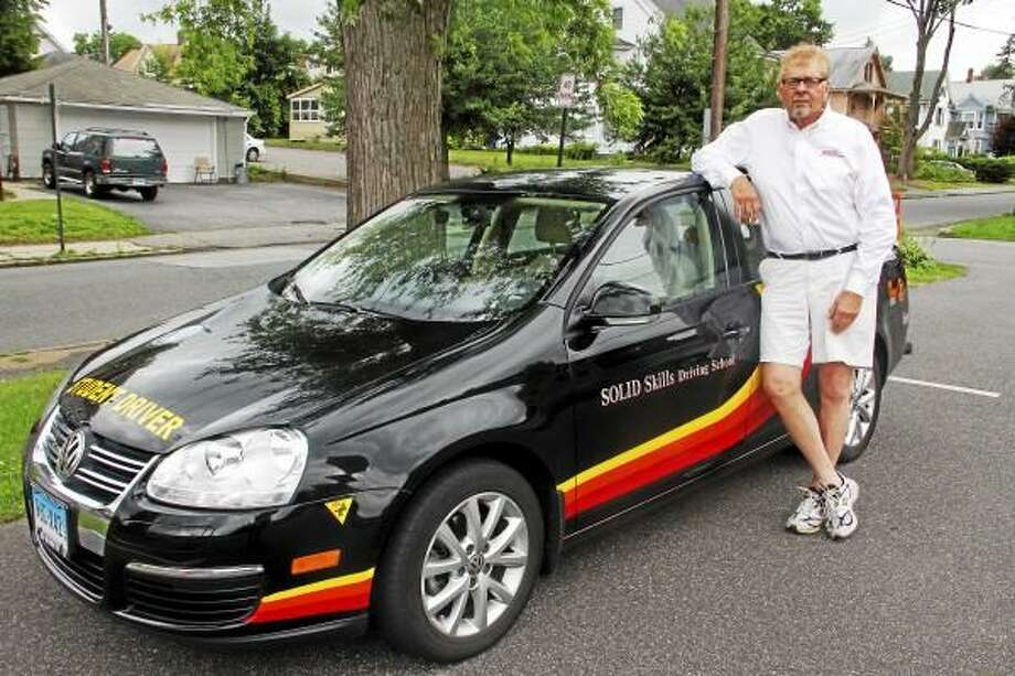 Kerry Washay, known as 'K Washay' to his students, stands next to the car he uses to instruct his driving students on Sunday, June 30, 2013. Washay said the purpose of his driving school is not for students to earn a license but to be safe and intelligent drivers. Esteban L. Hernandez - Register Citizen.