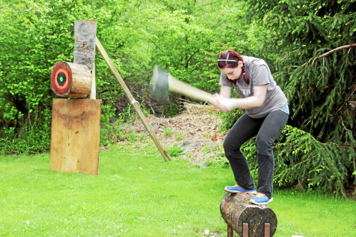 A Wamogo alum is chopping a log at the lumberjack demonstration.