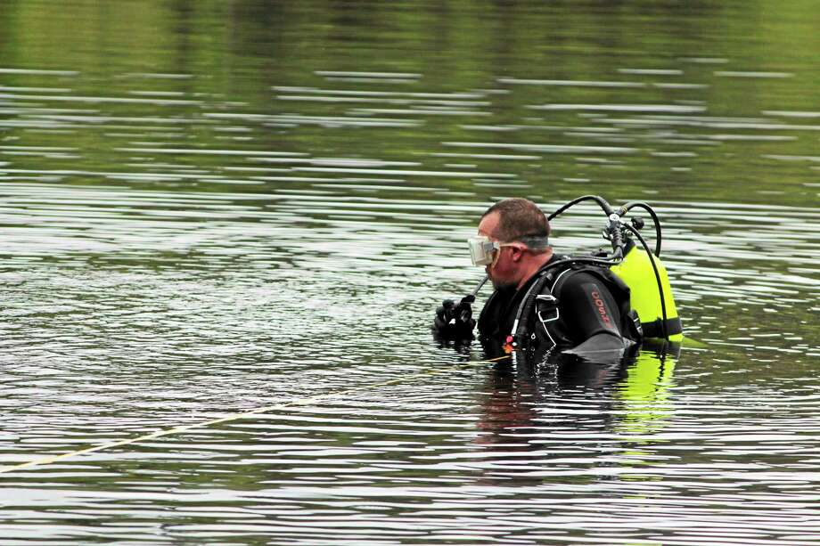 A diving team member was standing on top of the car underwater. Photo: (Shako Liu — The Register Citizen)
