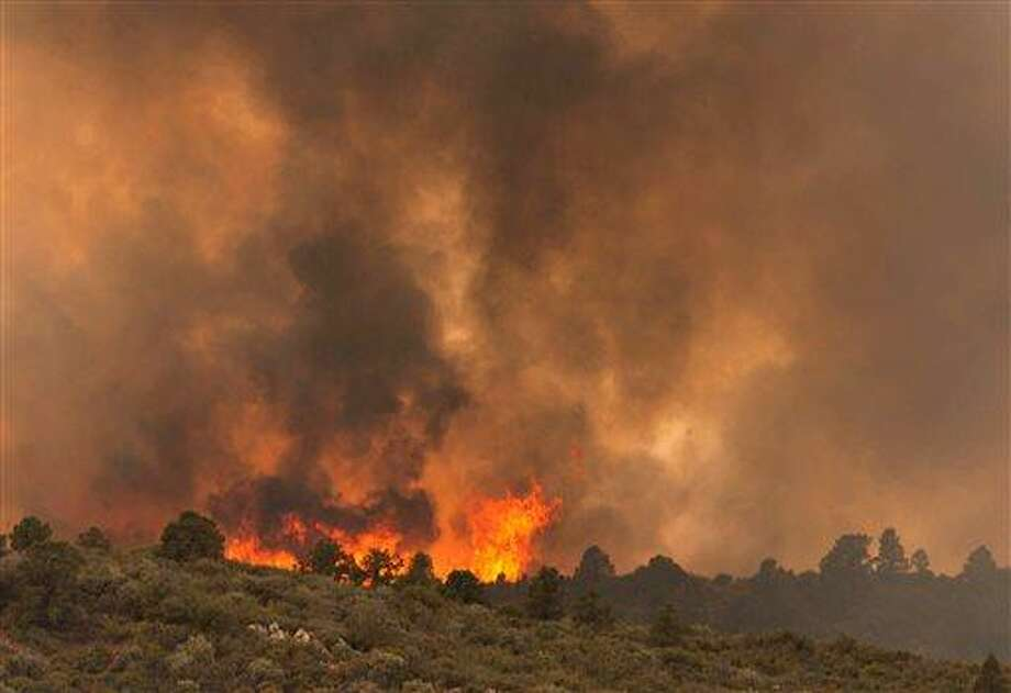 Flames top a ridge as the Yarnell Hill Fire moves towards Peeples Valley, Arizona on Sunday, June 30, 2013. (AP Photo/The Arizona Republic, Tom Story) Photo: AP / The Arizona Republic