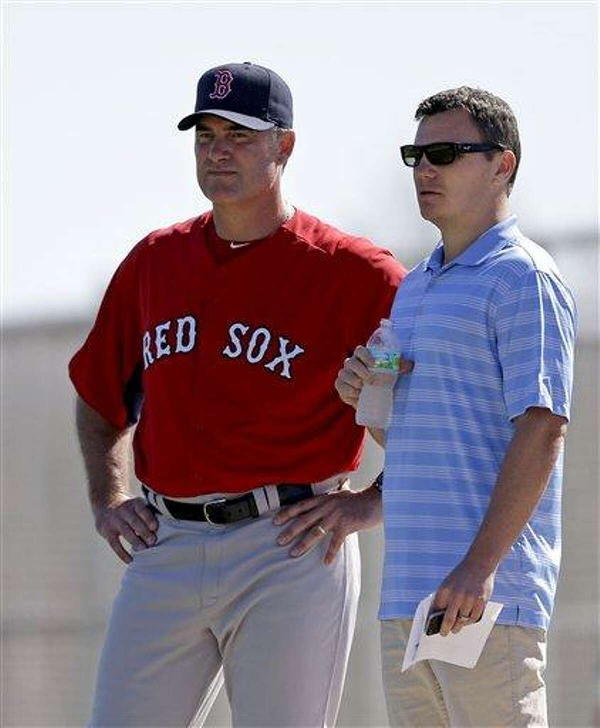 Boston Red Sox manager John Farrell, left, and general manager Ben Cherington, watch as Alfredo Aceves pitches batting practice during a spring training baseball workout, Wednesday, Feb. 20, 2013, in Fort Myers, Fla. (AP Photo/David Goldman)