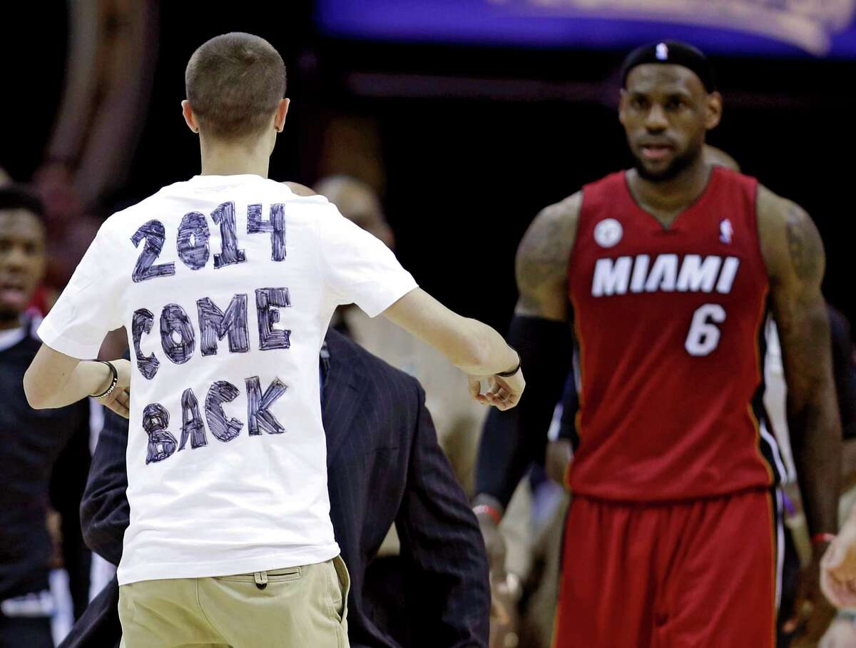 In this 2013 file photo, a fan runs out on the court towards Miami Heat's LeBron James during the fourth quarter of a game against the Cavaliers in Cleveland.