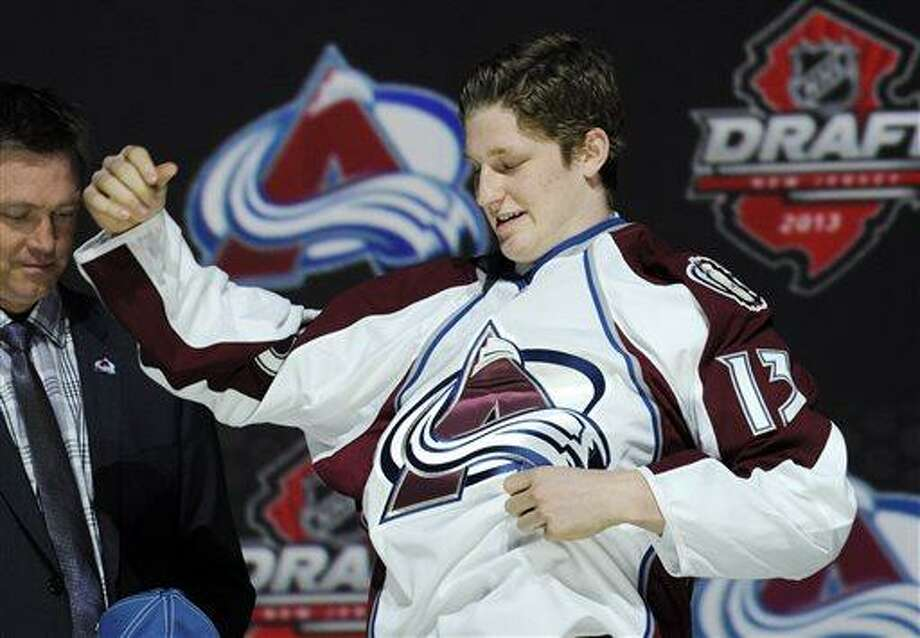 Nathan MacKinnon, a center, pulls on a Colorado Avalanche sweater after being chosen 1st overall in the first round of the NHL hockey draft, Sunday, June 30, 2013, in Newark, N.J. (AP Photo/Bill Kostroun) Photo: AP / FR59151 AP