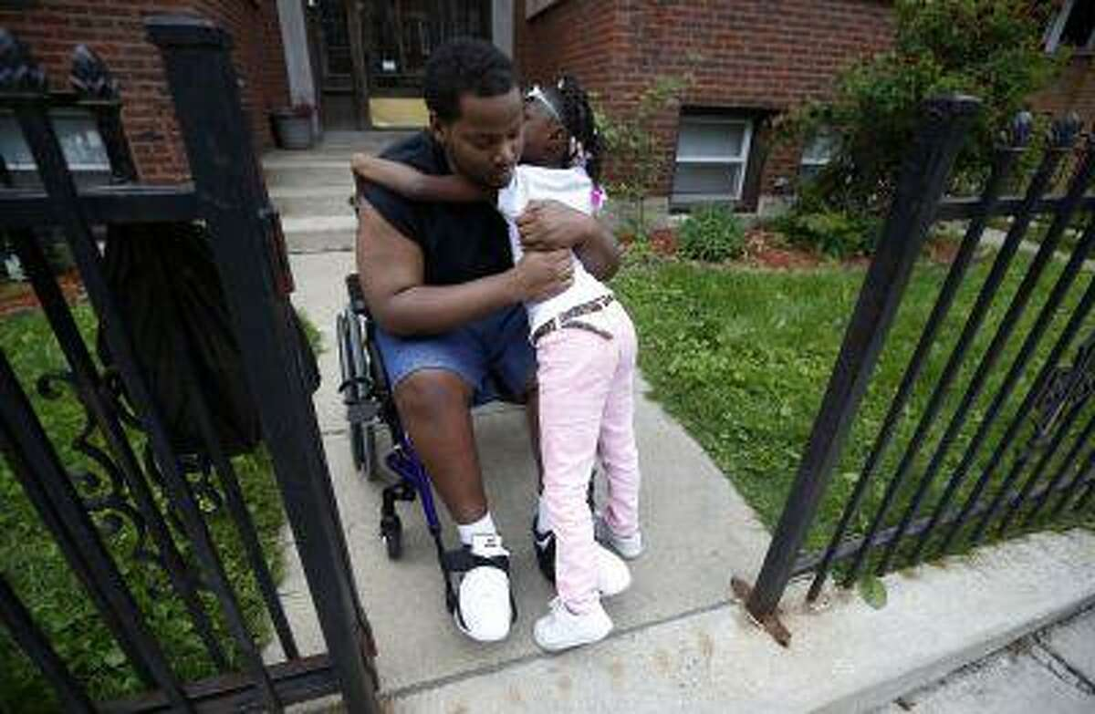 Miles Turner gets a hug from his cousin Sophia White at his home in Chicago, Illinois, June 9, 2013.