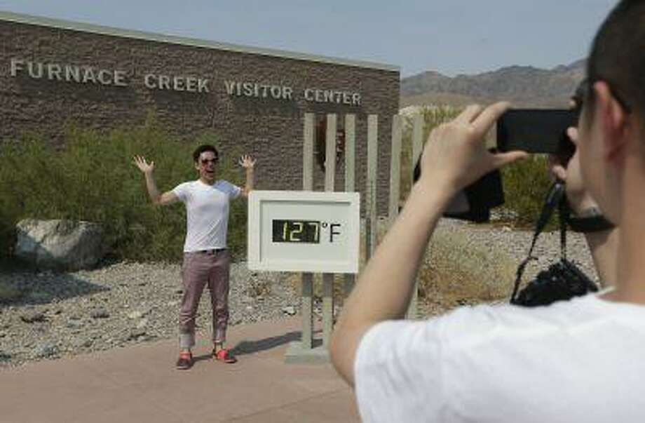 Cheng Jia, of china, right, takes a picture of Yongxin Yan by a digital thermometer at the Furnace Creek Vistitor Center in Death Vally National Park Friday, June 28, 2013 in Furnace Creek, Calif. Photo: AP / AP