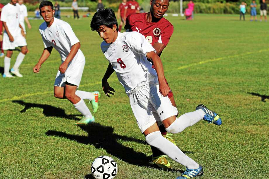 Torrington's Kevin Vaca dribbles the ball as Sacred Heart defends on Monday. Photo: Marianne Killackey — Special To Register Citizen  / 2014
