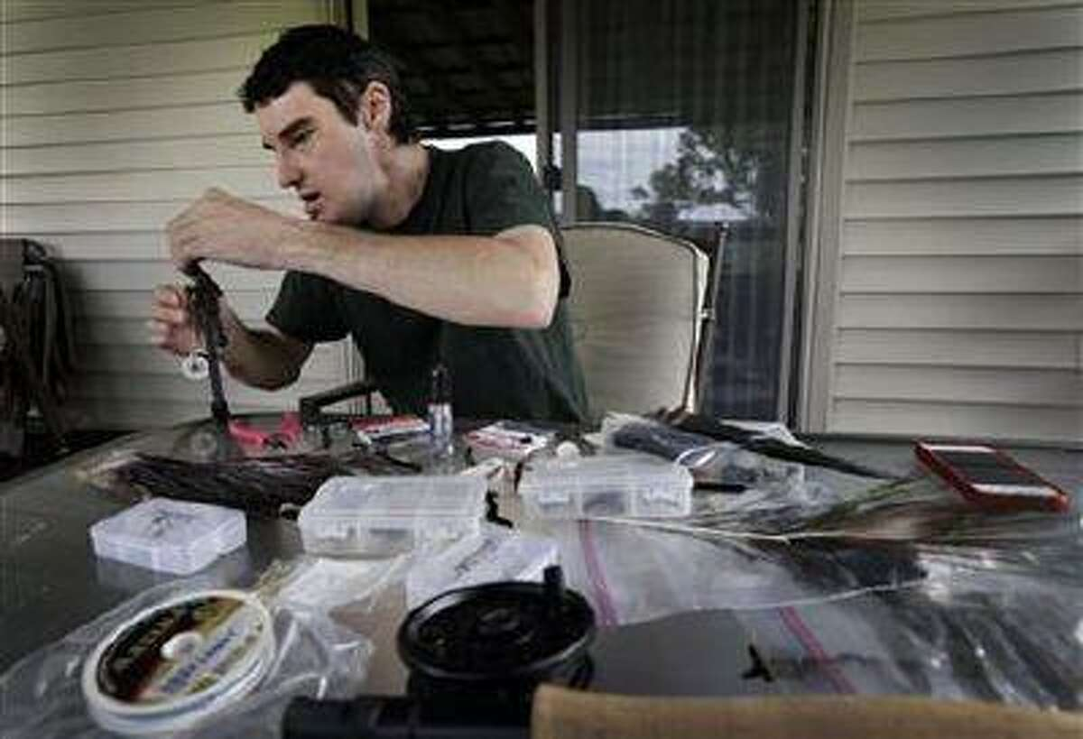In this June 25, 2013 photo, Richard Norris ties a fishing fly at his home in Hillsville, Va. The man whose face was disfigured by a gunshot spent 15 years as a recluse, but now the 38-year-old is doing things he never would have before. (Chuck Burton/AP)