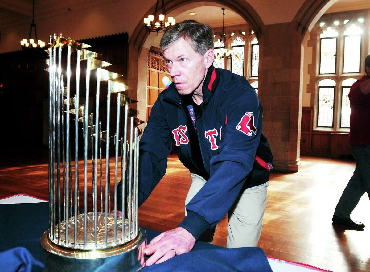 Arnold Gold — Register) Bill Wickman of the Red Sox security staff positions the 2007 World Series trophy on a table with the 2004 and 2013 trophies at the Yale Law School in New Haven on 1/27/2014.