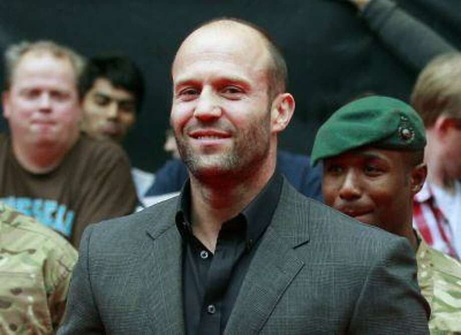 """In this Aug. 13, 2012 file photo, actor Jason Statham poses as he arrives for the UK premiere of Expendables 2 in London. In his latest film, """"Redemption,"""" the actor turns it up a notch, playing a homeless soldier on the streets of London. (AP Photo/Sang Tan, File) Photo: AP / AP"""