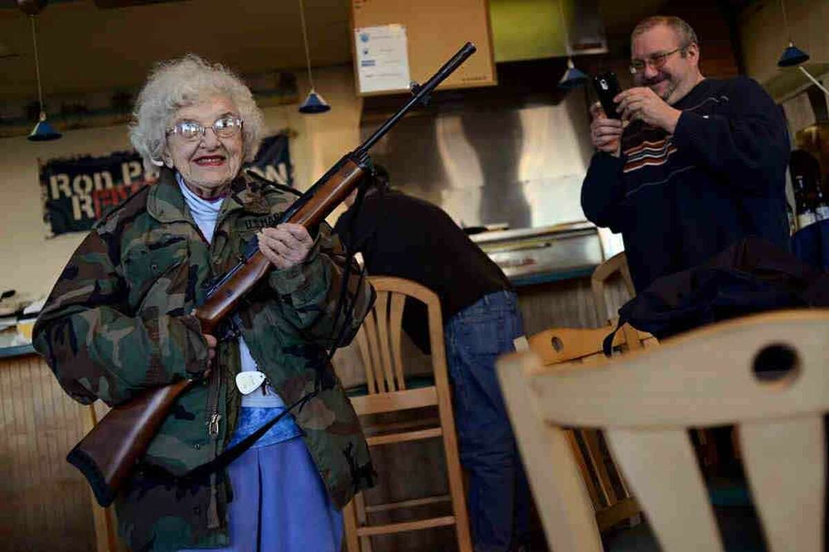 Lee Lazernick, right, asked his mother Thelma Lazernick, left, to pose with a customer's Ruger Mini-14 .223 semi-automatic rifle on Monday, Feb. 18, 2013, at All Around Pizza and Deli in Virginia Beach, Va., where customers wearing weapons or who bring their concealed weapons permit are offered a 15 percent discount. (AP Photo/The Virginian-Pilot, Amanda Lucier)