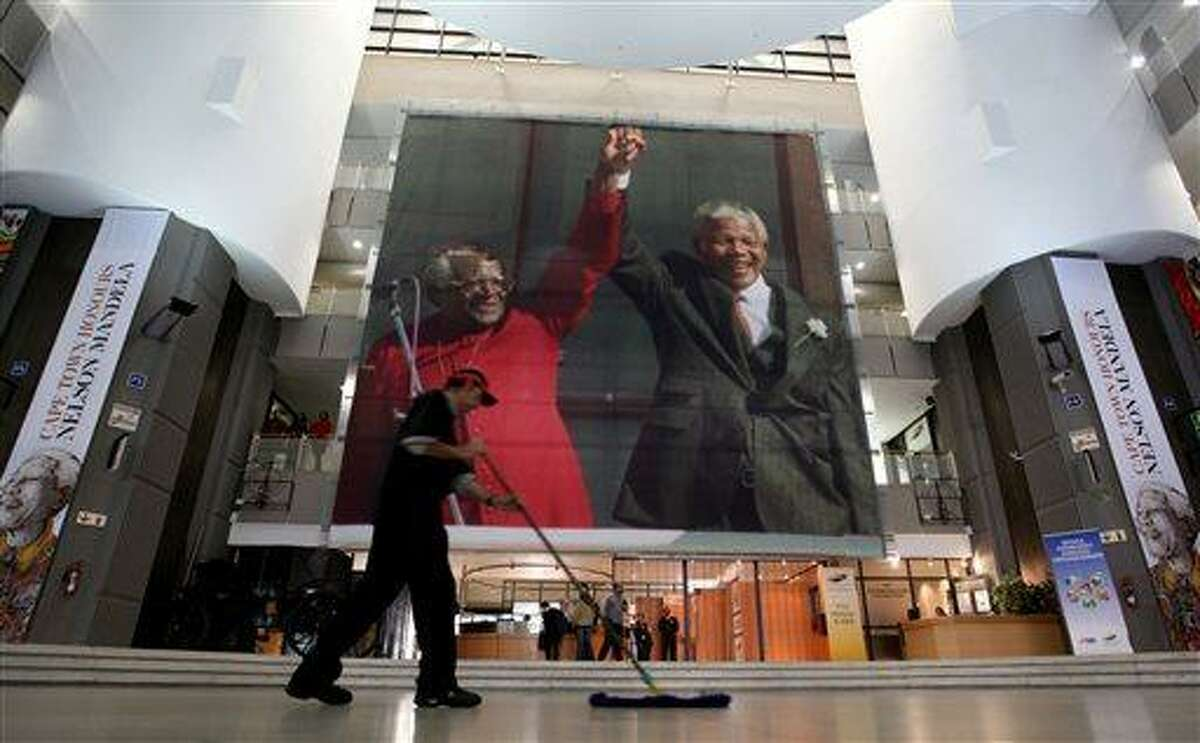 FILE - In this Thursday June 27, 2013, file photo, giant photographs of former president Nelson Mandela are displayed at the Nelson Mandela Legacy Exhibition at the Civic Centre in Cape Town, South Africa. President Jacob Zuma canceled a trip to Mozambique on Thursday in an indication of heightened concern about Mandela, whose health deteriorated last weekend. (AP Photo/File)