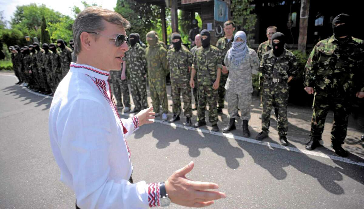Oleh Lyashko, left, leader of Ukrainian Radical Party and presidential candidate, speaks to self defense volunteers at a training ground outside Kiev, Ukraine, Friday, May 23, 2014. Ukraine is holding a presidential election Sunday but it has become downright dangerous for many in the east to be associated with the vote, since the eastern regions of Donetsk and Luhansk declared independence last week. Ukrainian police and election officials accuse pro-Russia gunmen there of seizing election commission offices and threatening members in an effort to derail the presidential vote. (AP Photo/Osman Karimov)