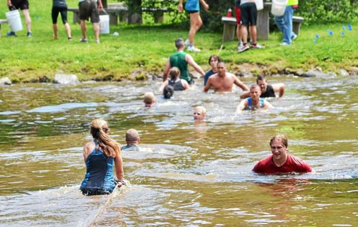Runners cross the pond during the 5k WYLD Mud Run at the John A Minetto State Park on Saturday. The event is a fundraiser for the Northwest CT YMCA. John Berry - Register Citizen.