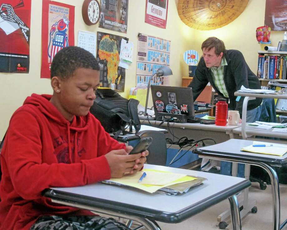 In this Tuesday, Jan. 14, 2014 photo Kiante Hampton, left, logs onto Twitter for a classroom exercise as teacher Chris Lazarski, right, monitors the conversation at Wauwatosa West High School in Wauwatosa, Wis. While many school officials frown upon the use of social media in the classroom, an increasing number of teachers see Twitter as a way to expand a classroom discussion to include diverse viewpoints from students around the country. Photo: Dinesh Ramde—The Associated Press  / AP