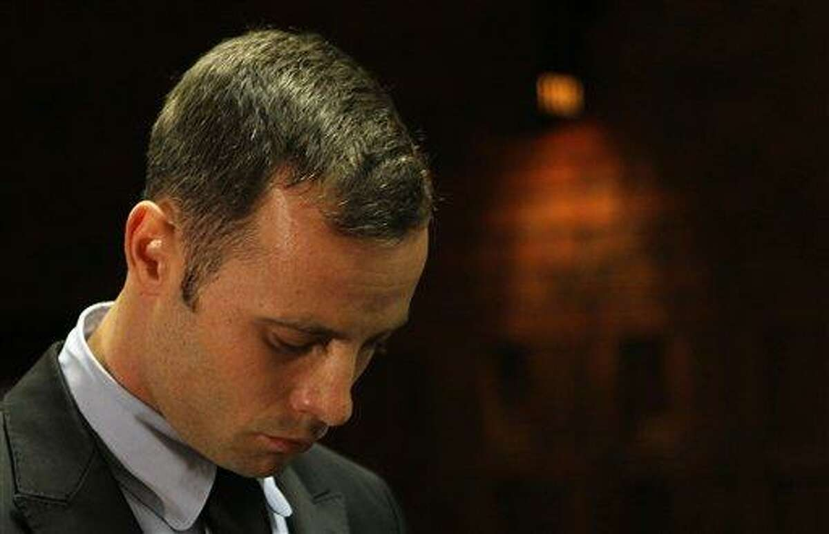 Olympic athlete Oscar Pistorius stands inside the court as a police officer looks on during his bail hearing at the magistrate court in Pretoria, South Africa, Wednesday, Feb. 20, 2013. A South African judge says defense lawyers will need to offer