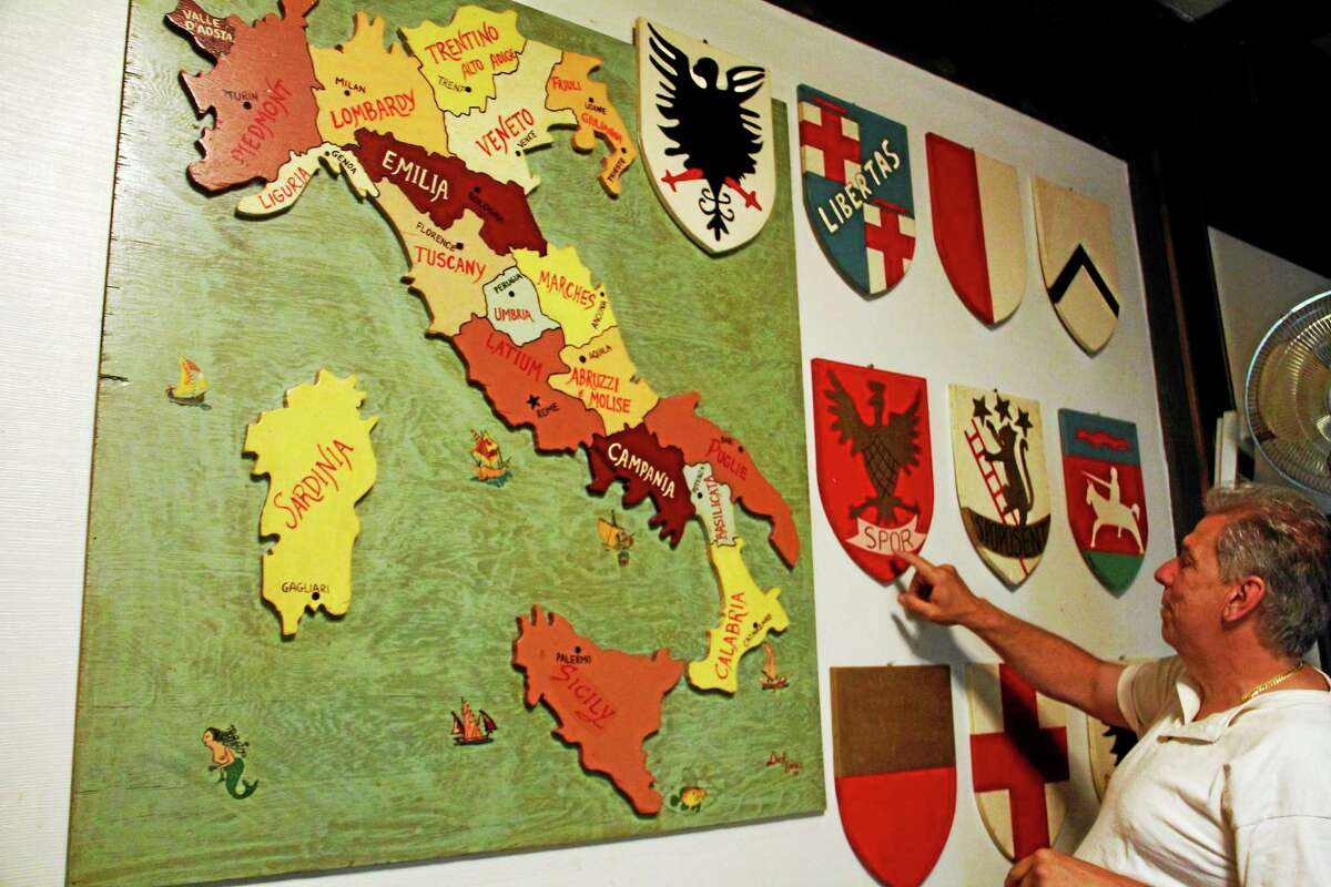 Club president Bruce Harrison points at an art display with a map of Italy and coat of arms inside the Order of the Sons of Italy on Center Street on June 24 in Torrington.