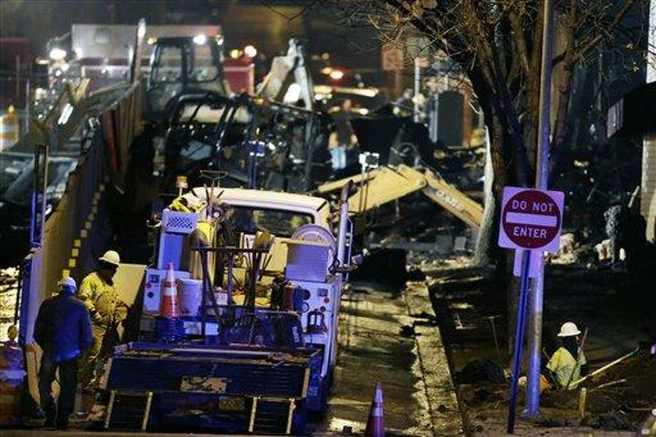 Utility workers repair gas lines near a building that exploded and caught fire in the Plaza shopping district of Kansas City, Mo., Tuesday, Feb. 19, 2013. (AP Photo/Orlin Wagner) Photo: AP / AP