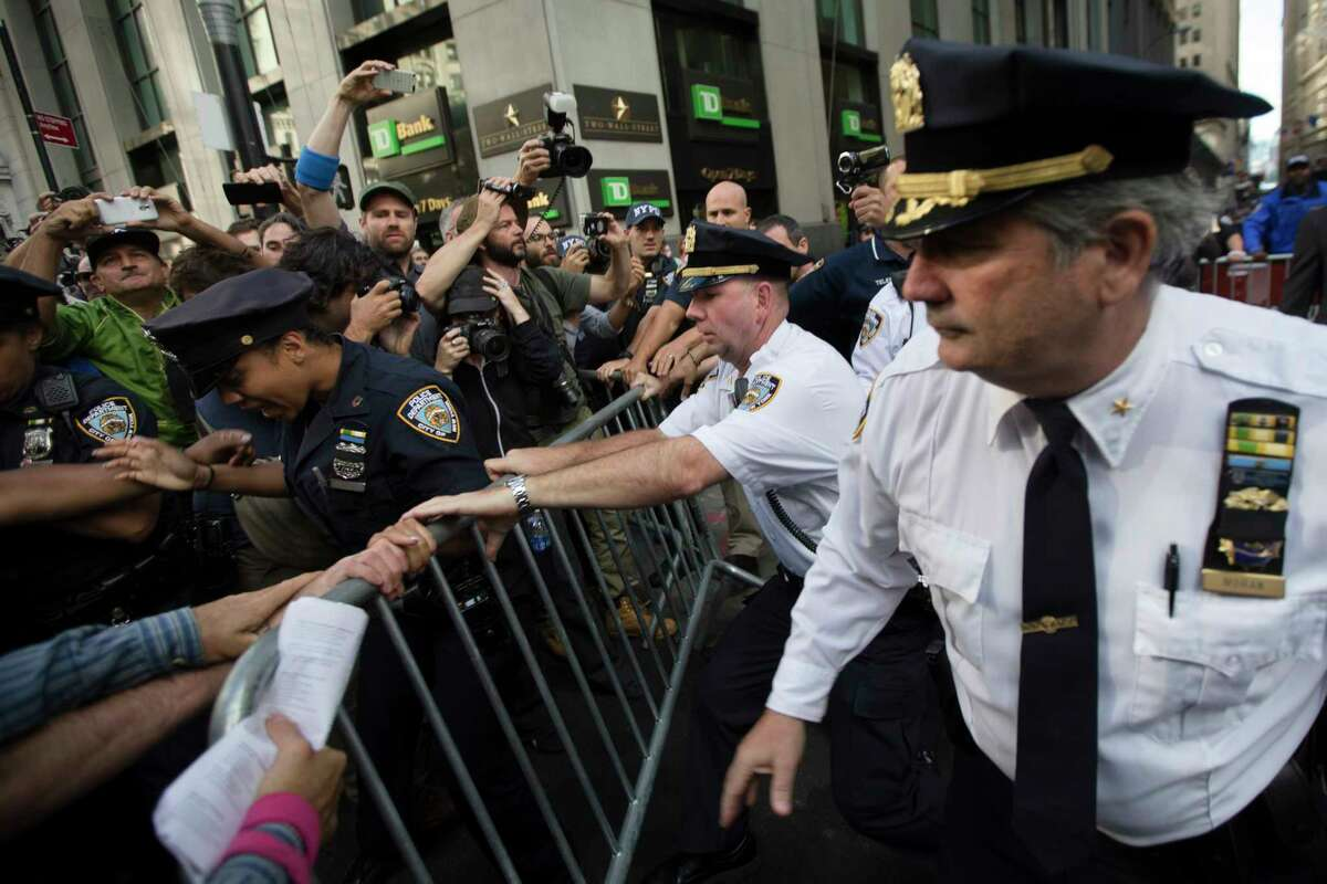 Police move to secure a barricade being wrestled away by protestors during a march demanding action on climate change and corporate greed, Monday, Sept. 22, 2014, a day after a huge climate march in New York.