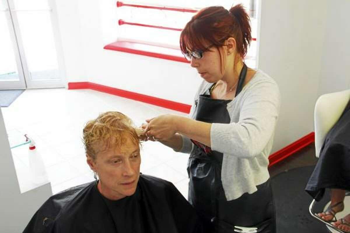 Jody Dlugokinski styles a woman's hair on Saturday, June 29, at the newly opened Oasis Salon on 264 Main Street in Torrington. Esteban L. Hernandez Register Citizen