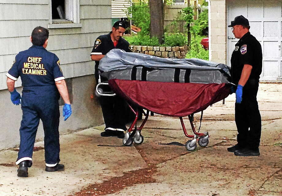 Members of the state's Chief Medical Examiner's office remove a body from 34 North Elm St., one of Torrington's sober houses, Friday. Photo: Isaac Avilucea — The Register Citizen