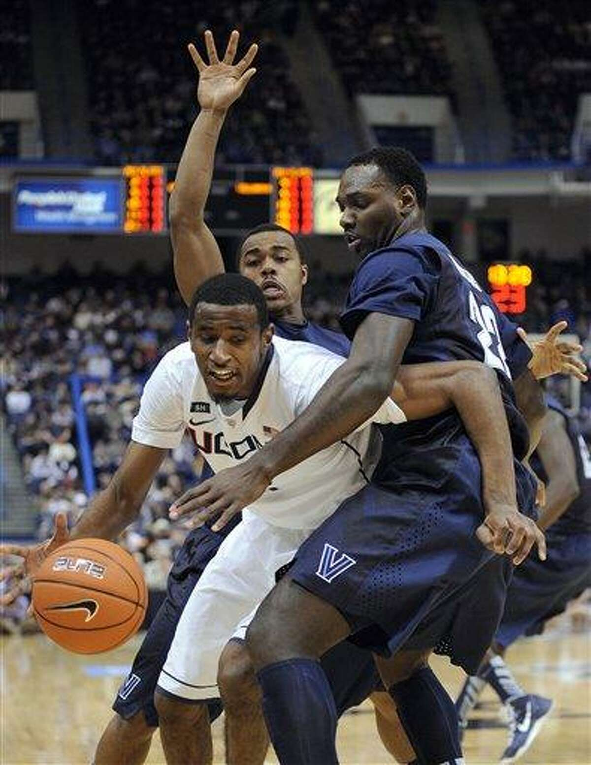 Connecticut's DeAndre Daniels is guarded by Villanova's JayVaughn Pinkston, right, and Tony Chennault during the first half of an NCAA college basketball game in Hartford, Conn., Saturday, Feb. 16, 2013. Villanova won the game 70-61. (AP Photo/Fred Beckham)