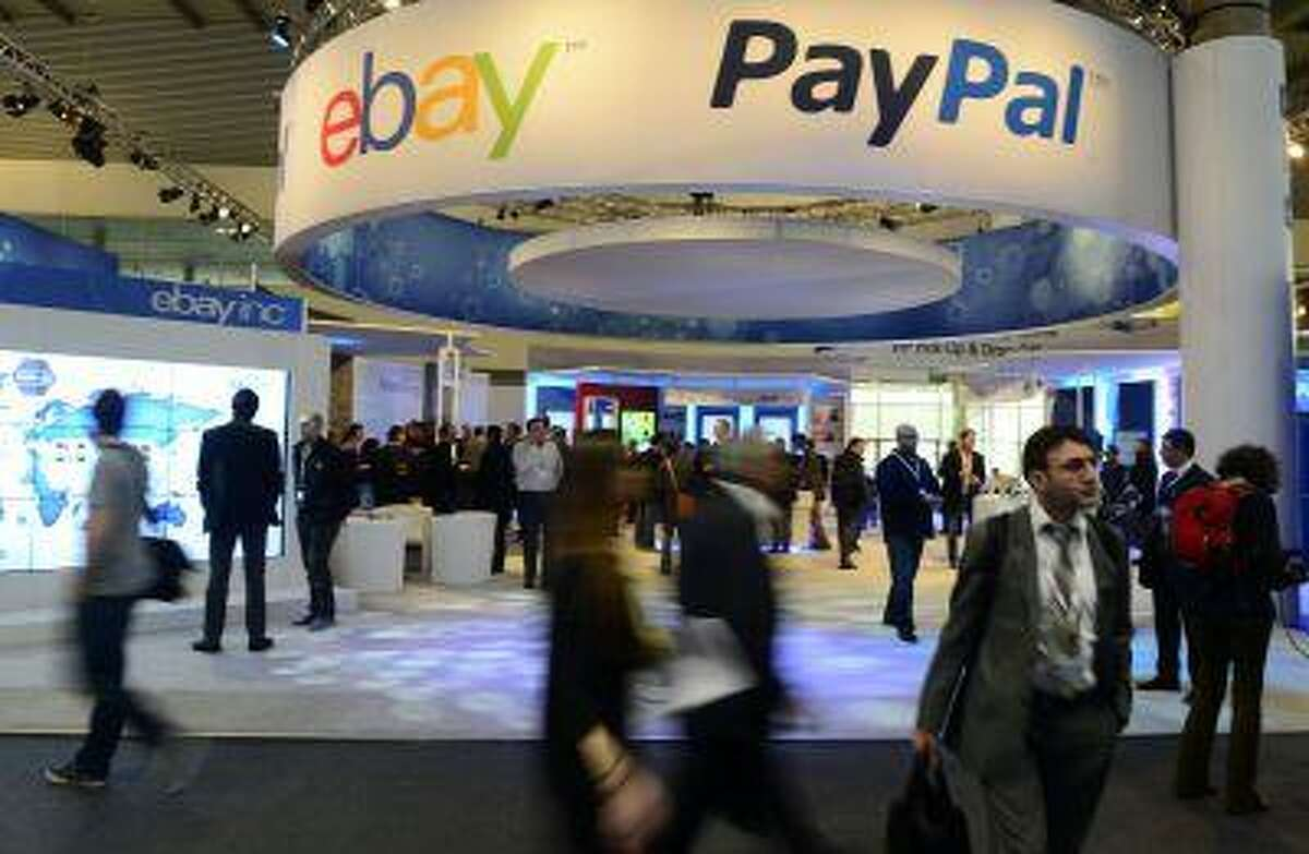 Attendees walks in front of a Paypal stand at the Mobile World Congress, the world's largest mobile phone trade show, in Barcelona, Spain, Wednesday, Feb. 27, 2013. (AP Photo/Manu Fernandez)