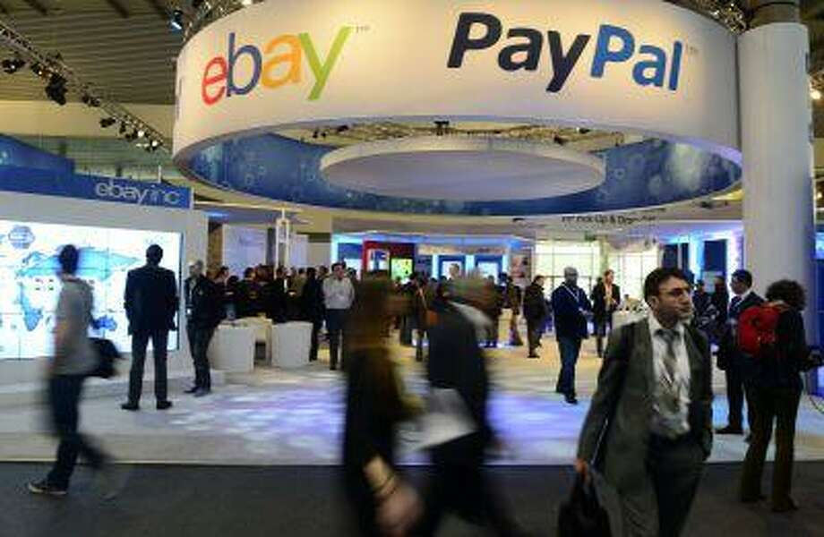 Attendees walks in front of a Paypal stand at the Mobile World Congress, the world's largest mobile phone trade show, in Barcelona, Spain, Wednesday, Feb. 27, 2013. (AP Photo/Manu Fernandez) Photo: ASSOCIATED PRESS / AP2013