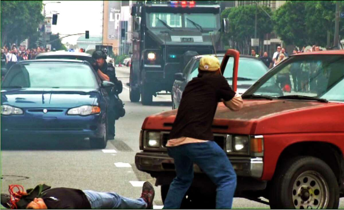 In this July 6, 2013 still frame from a video produced by the Los Angeles Police Department, as police take part in a counterterrorism drill. A Lenco Bearcat, an armored vehicle purchased by the LAPD from a Massachusetts firm that builds them for a variety of military and police uses, stands at the rear.