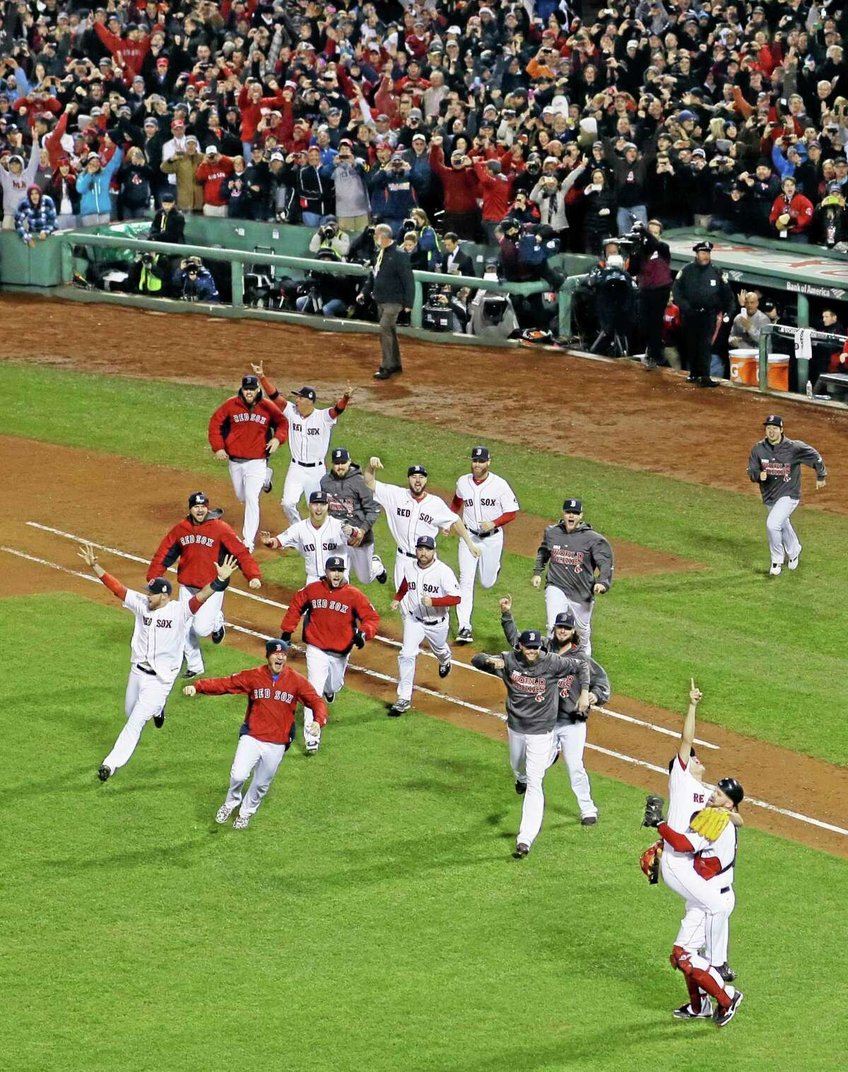 Boston Red Sox relief pitcher Koji Uehara jumps into David Ross's arms after striking out St. Louis Cardinals second baseman Matt Carpenter (13) in Game 6 of baseball's World Series Wednesday, Oct. 30, 2013, in Boston. The Red Sox won 6-1 to win the series. (AP Photo/Matt Slocum)