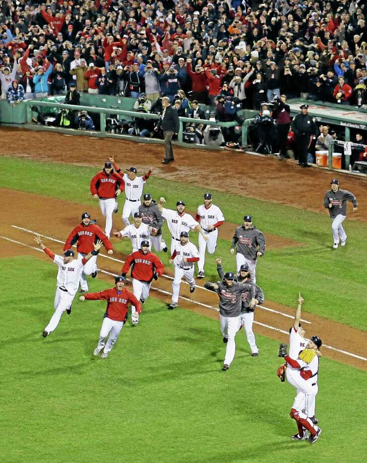 Boston Red Sox relief pitcher Koji Uehara jumps into David Ross's arms after striking out St. Louis Cardinals second baseman Matt Carpenter (13) in Game 6 of baseball's World Series Wednesday, Oct. 30, 2013, in Boston. The Red Sox won 6-1 to win the series.  (AP Photo/Matt Slocum) Photo: AP / AP