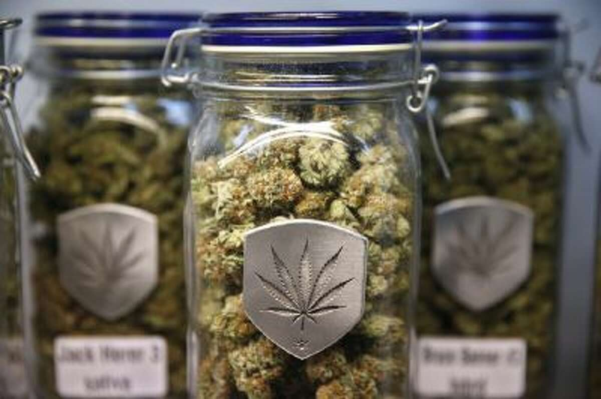 Different strains of pot are displayed for sale at Medicine Man marijuana dispensary in Denver, Colo., where pot became legal Jan. 1.