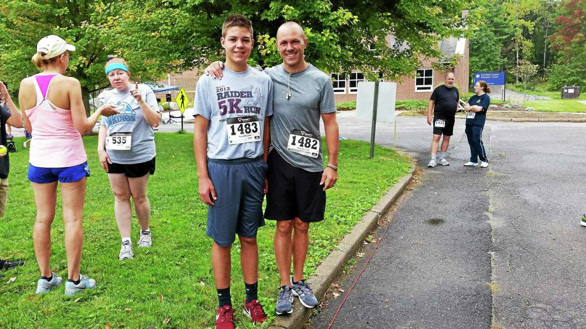 N.F. Ambery - Special to the Register Citizen Aiden Mattiello, 16, of Torrington High School, who came in second place during Sunday's Mile 4 Moe 5K race, stands with his father, Brian, 48, of Torrington. The race was held at the University of Connecticut Torrington campus and raised money for Camp Moe.