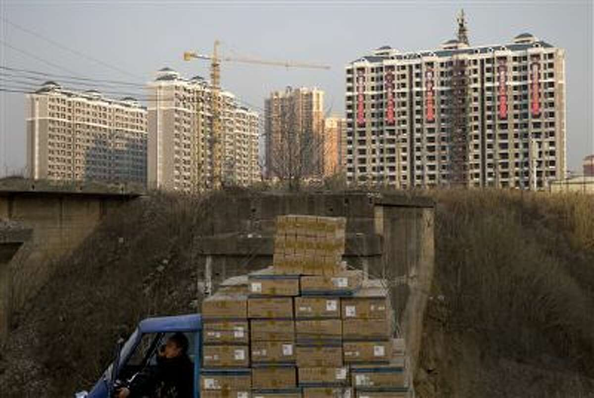 A man talks on a mobile phone inside his tricycle cart loaded with goods near under-construction residential buildings in Changsha, in China's Hunan province. U.S. investors are being hit with new worries from overseas just as the economy at home appears to be strengthening. (AP Photo/Andy Wong, File)