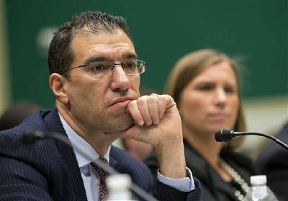 Andrew Slavitt, group executive vice president for Optum/QSSI, left, and Lynn Spellecy, corporate counsel for Equifax Workforce Solutions, listen to questioning during a House Energy and Commerce Committee hearing with contractors that built the federal government's health care websites. Photo: AP / AP