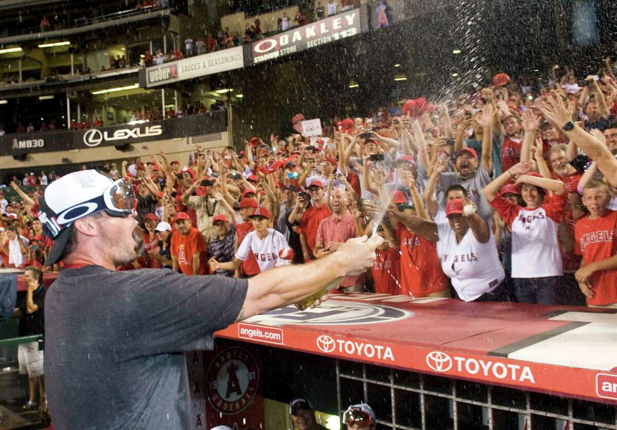Los Angeles Angels third baseman David Freese sprays the crowd with champagne after the Halos clinched the American League West on Wednesday at Angel Stadium.