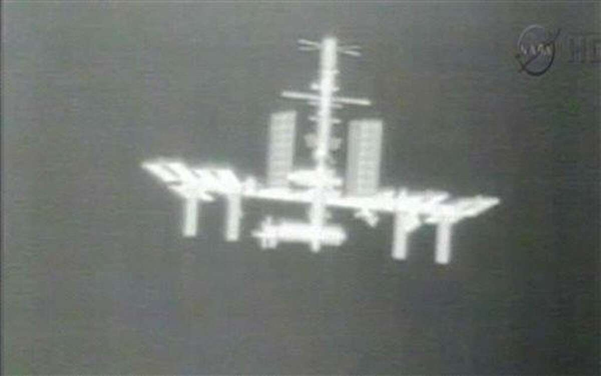 FILE - This Thursday, May 24, 2012 image made from video provided by NASA-TV shows the International Space Station taken from the thermal imaging camera aboard the SpaceX Dragon commercial cargo craft as it approaches the station. NASA says the International Space Station has lost contact with NASA controllers in Houston Tuesday morning, Feb. 19, 2013. Officials say the six crew members and station are fine and they expect to fix the problem soon. NASA said something went wrong during a computer software update on the station. (AP Photo/NASA)