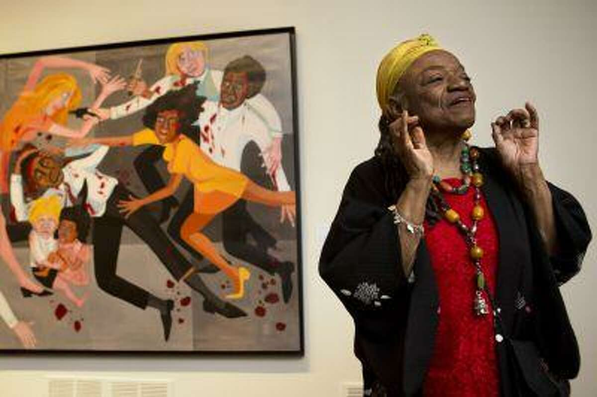 Artist Faith Ringgold talks about her artwork in front of her painting,