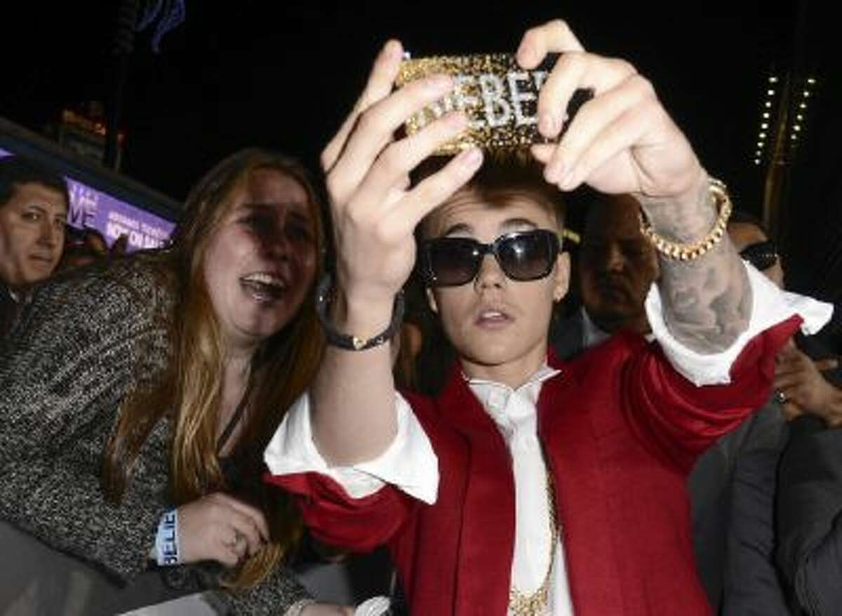 In this Dec. 18, 2013 file photo, singer Justin Bieber takes a selfie with a fan at a premiere in Los Angeles.
