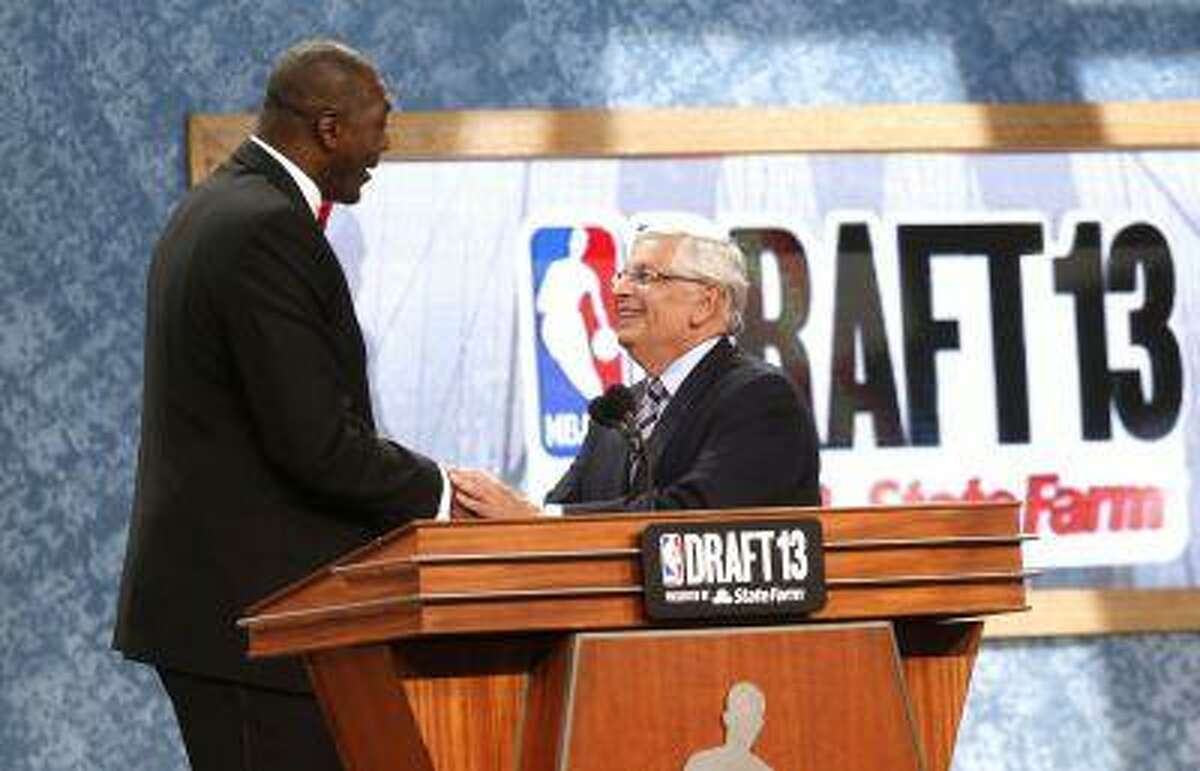 Retired NBA star Hakeem Olajuwan, left, shakes hands with NBA Commissioner David Stern after coming onstage to pay tribute to him at the end of the first round of the NBA basketball draft, Thursday, June 27, 2013, in New York.