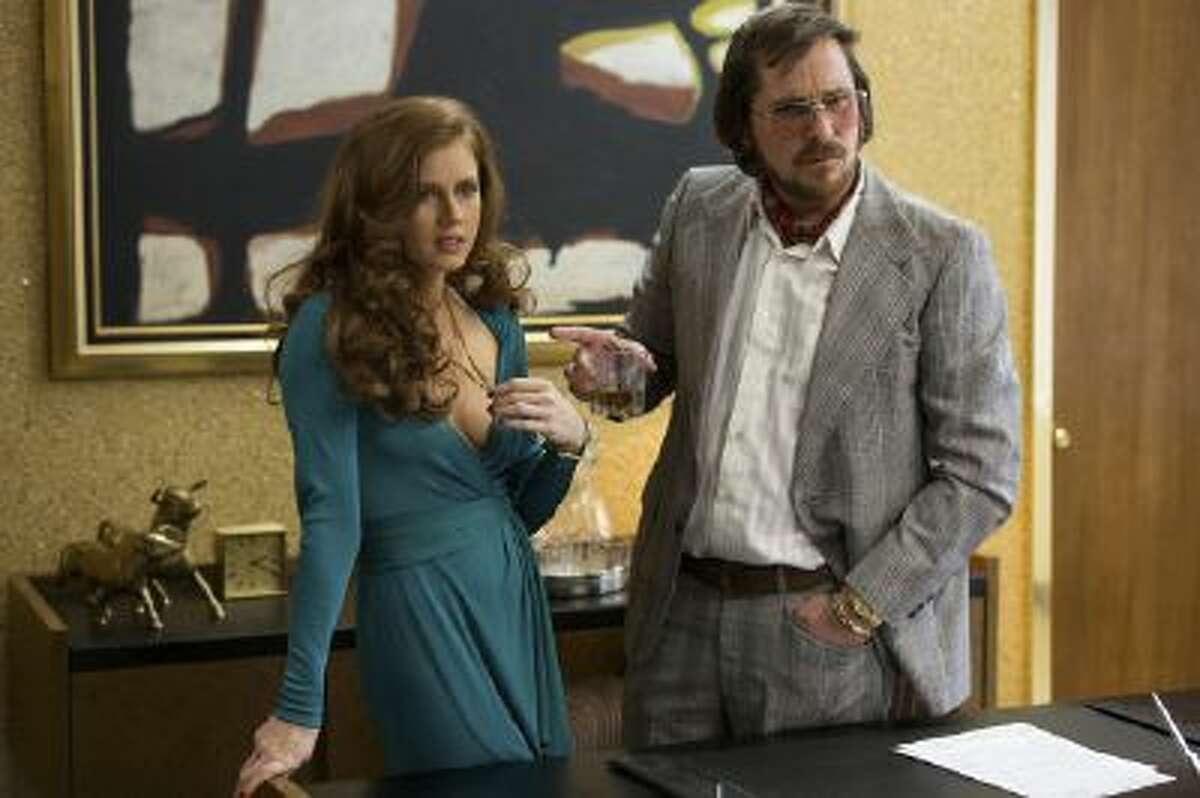 Sydney Prosser (Amy Adams, left) and Irving Rosenfeld (Christian Bale) attempt to scam an under cover agent in Columbia Pictures'