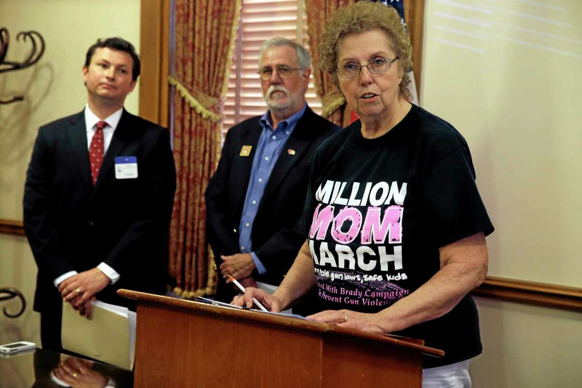 As Brady Center attorney Robert Wilcox Jr., left, and Bryan Miller, second left, with Heeding God's Call, an activist group to end gun violence, listen, Carole Stiller, with New Jersey Million Mom March chapters of the Brady campaign to prevent gun violence, addresses a gathering in Trenton, N.J., Monday, May 19, 2014, as they announce that the groups are suing New Jersey over the state's 12-year-old
